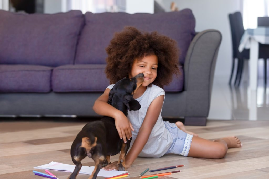 Girl playing on the floor with her dachshund